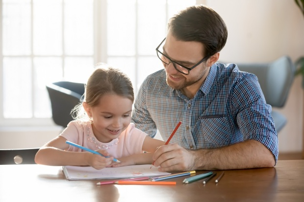 Young dad drawing pictures in paper album with small daughter.