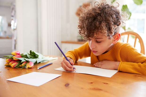 Young Boy At Home With Bunch Of Flowers Writing In Mothers Day Card