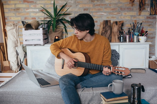 young man playing guitar in his home