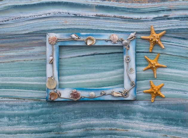 sea wooden frame with shells on sea background
