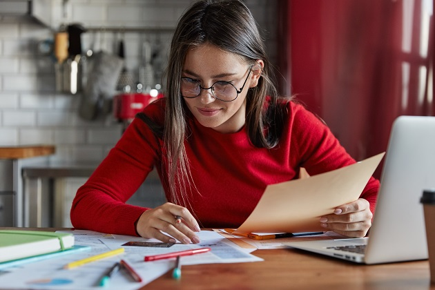 Horizontal shot of cheerful woman sits at kitchen table reviews finances, sits in front of opened laptop, wears red turtleneck sweater, makes notes in papers, cuts off expenses. Domestic interior